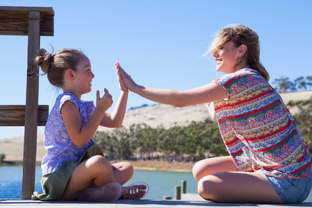 pat down: Mother and daughter playing pat a cake LANG_EVOIMAGES
