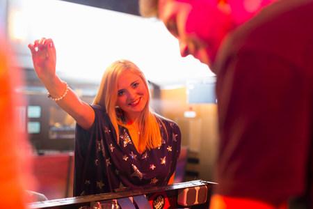 impressed: Woman standing in front of disc jockeys mixing desk