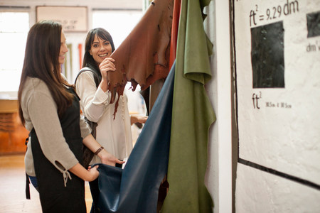 salespeople: Shop assistant and customer looking at leather LANG_EVOIMAGES