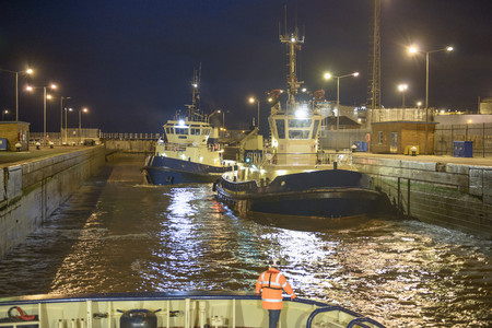 Tugboats docked in harbor at night