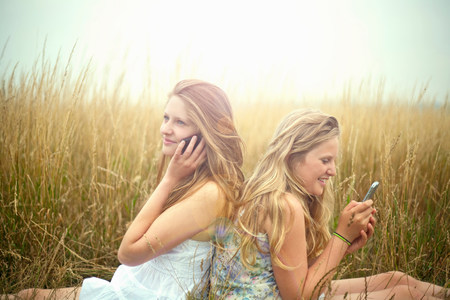 two persons only: Girls using smartphones in a field,back to back