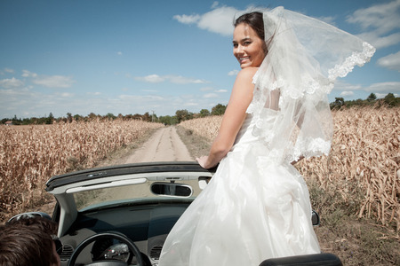 Newlywed couple driving in convertible