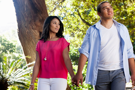 bi: Young couple holding hands with trees in background