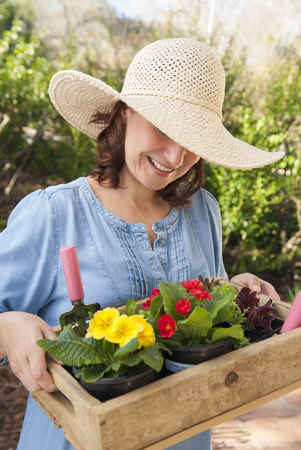 gratify: Woman carrying wooden box of flowers