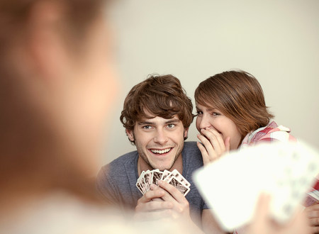 Young couple playing cards and whispering LANG_EVOIMAGES
