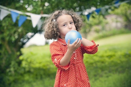 socializando: Chica soplando globo al aire libre