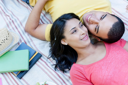Young couple lying on picnic blanket LANG_EVOIMAGES