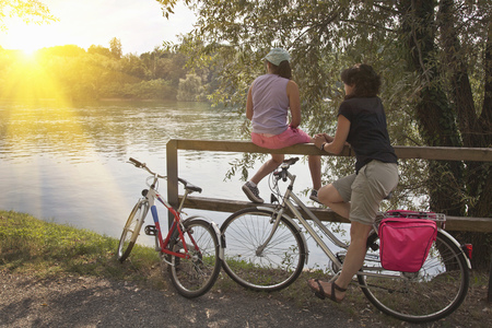 preadolescent: Women with bicycles relaxing by river
