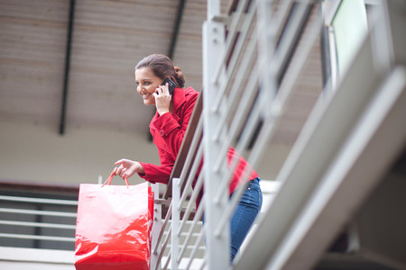 Young woman on cellphone in shopping mall LANG_EVOIMAGES