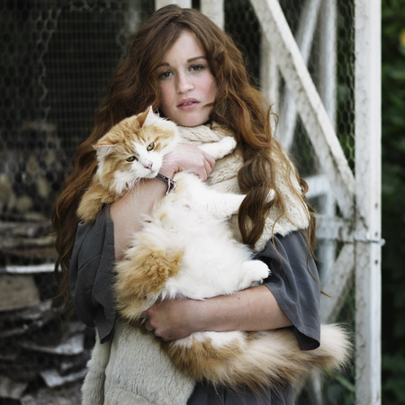 somber: Woman holding large cat outdoors
