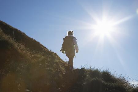 ascends: Woman hiking on rural hillside