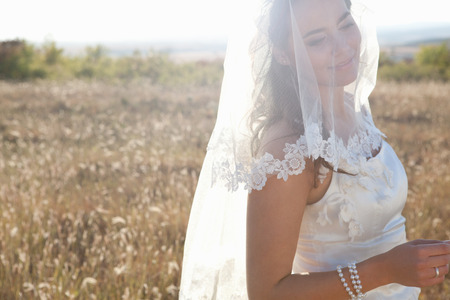 Newlywed bride standing outdoors LANG_EVOIMAGES