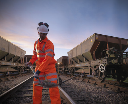 Railway worker shoveling on train tracks