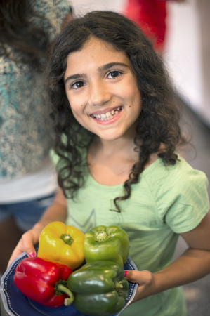 Smiling girl holding bowl of peppers