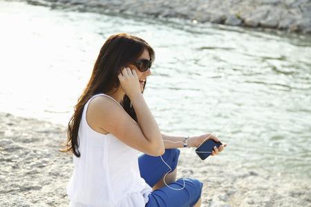 Woman listening to headphones on beach