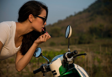 narcissist: Woman applying lipstick in wing mirror of moped