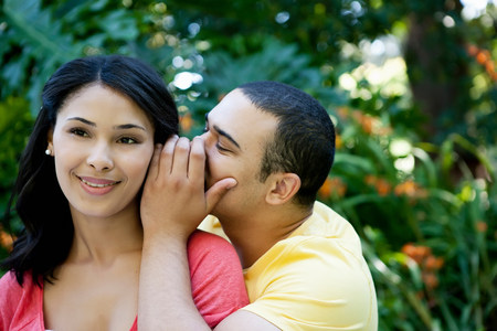 Young man whispering in womans ear LANG_EVOIMAGES