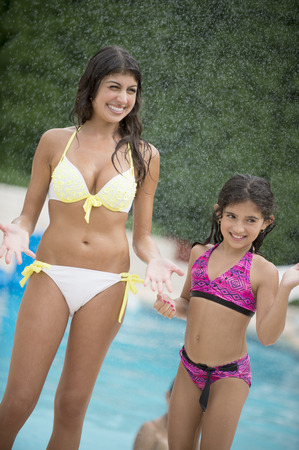 Sisters standing by swimming pool