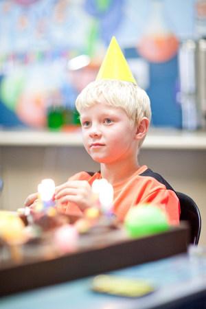personas festejando: Chico en fiesta de cumpleaños con sombrero de fiesta