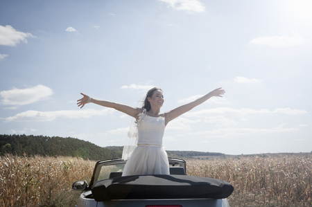 obligations: Newlywed bride standing in convertible