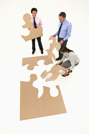 concluded: Business people assembling puzzle