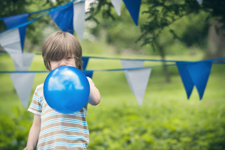 children party: Boy blowing up balloon outdoors LANG_EVOIMAGES