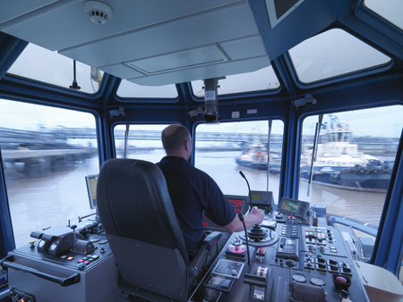 industrialization: Worker driving tugboat in wheelhouse