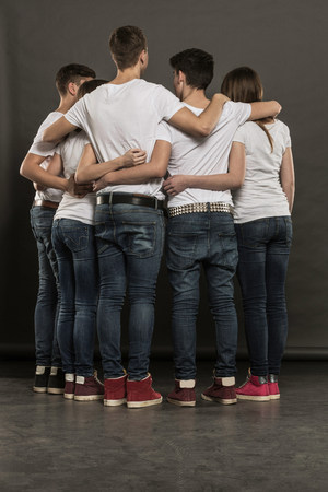 Rear view of five teenagers in huddle LANG_EVOIMAGES