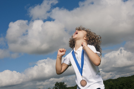 enthusiastically: Girl with medal cheering outdoors LANG_EVOIMAGES