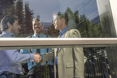 agrees: Businessmen shaking hands in office
