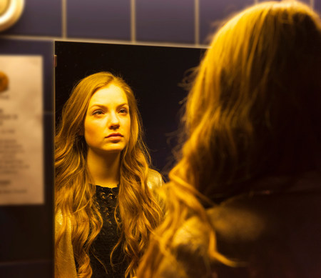 Teenage girl looking at her reflection in mirror LANG_EVOIMAGES