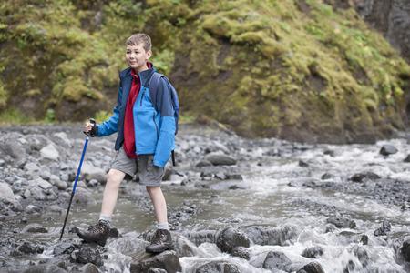 Boy hiking on rocky river LANG_EVOIMAGES