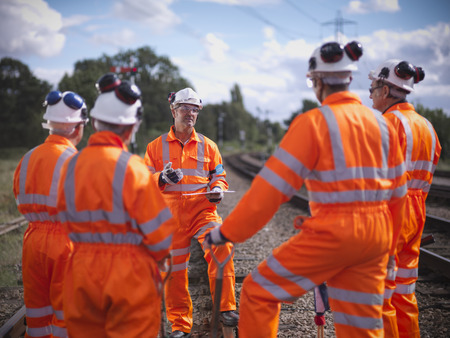 communications tools: Railway workers talking on train tracks