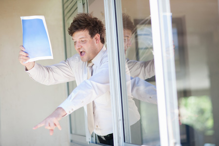 communicated: Businessman shouting from office window LANG_EVOIMAGES