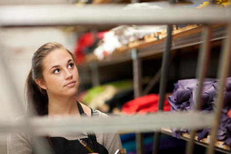 salespeople: Young woman working in leather stockroom