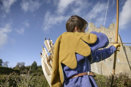 niños vistiendose: Student in period dress shooting arrow