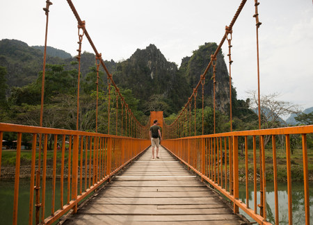 Man on bridge over river,Vang Vieng,Laos LANG_EVOIMAGES