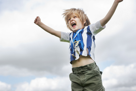 successes: Boy with medals cheering outdoors LANG_EVOIMAGES