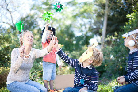 woman hanging toy: Mother and boys playing outdoors