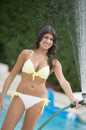 Woman spraying water hose outdoors