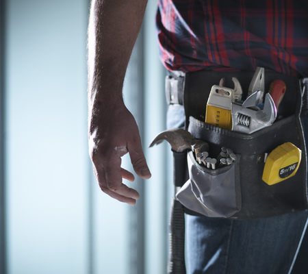 crescent wrench: Close up of worker wearing tool belt