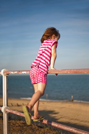 travel features: Little girl on railings by beach