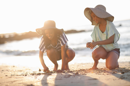 Women drawing in sand on beach