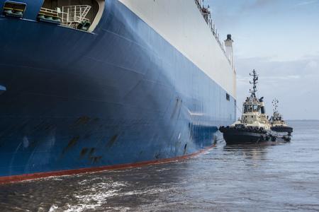Tugboats pushing car ship