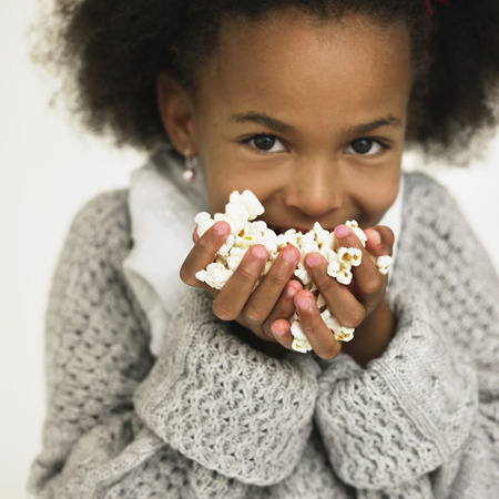 nourishing: Girl eating handful of popcorn