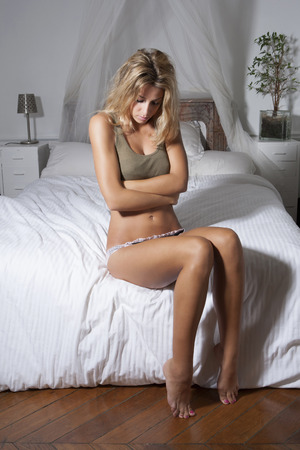 posed: Woman clutching her belly on bed