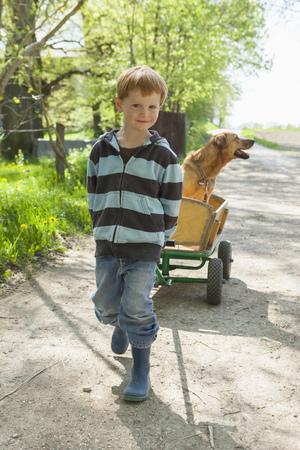 omnivore: Boy pulling cart with dog LANG_EVOIMAGES