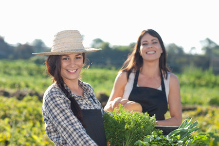 looking at viewer: Women with vegetables grown at farm