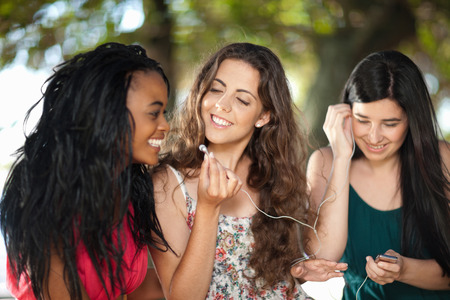 Women listening to earphones outdoors
