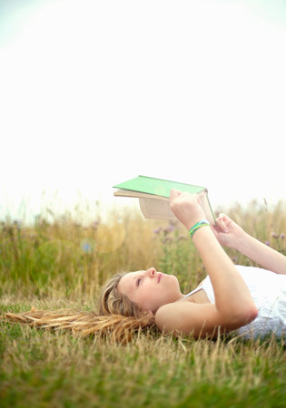 Teen girl lying in field,reading book LANG_EVOIMAGES